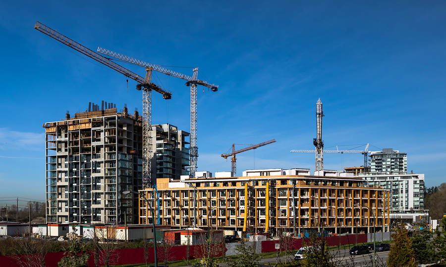 Wide view of multifamily residential construction sites in a city with multiple cranes against a blue sky
