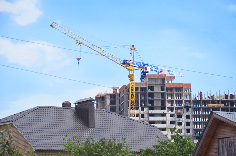 Apartment building under construction with house roof in foreground