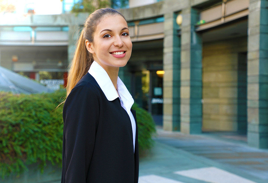 Smiling young woman in business dress in front of office