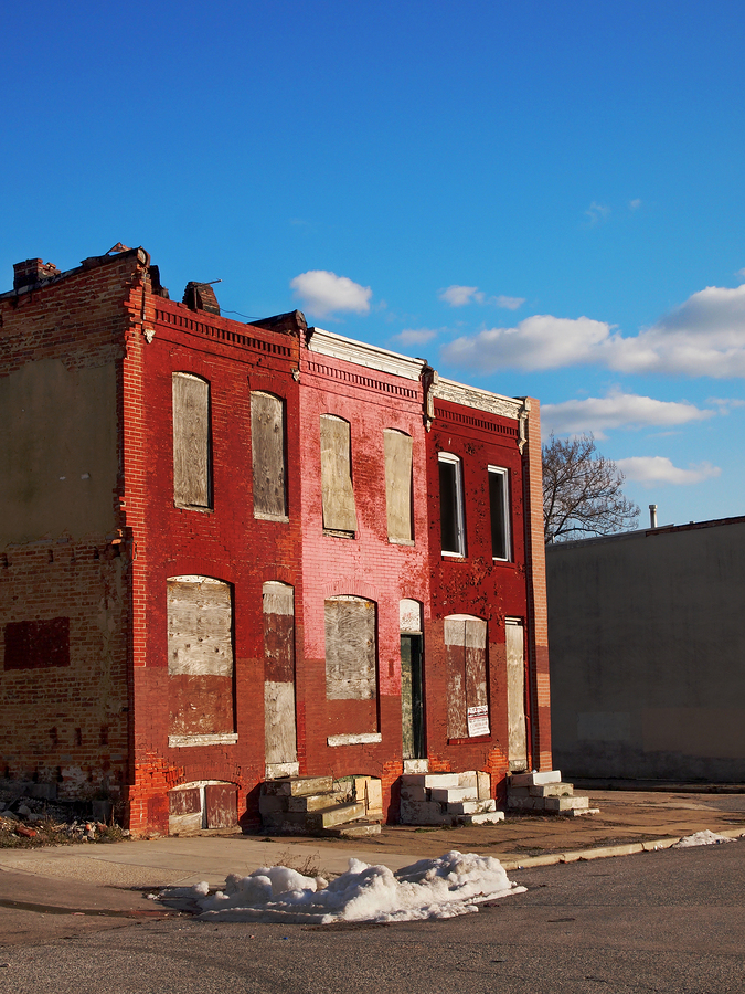 Abandoned block of rowhouses against a blue sky
