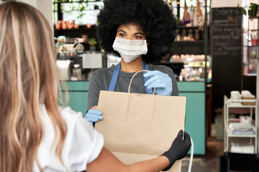 Black woman wearing surgical mask and gloves with beautiful 4C hair hands takeout bag to white woman customer in gloves